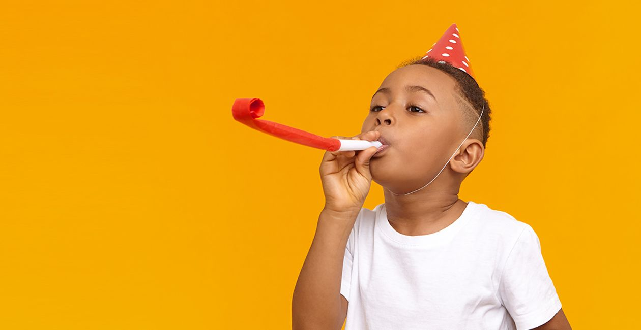 Happy boy celebrating a birthday, posing isolated at blank yellow wall, blowing whistle, Birthday hat on his head