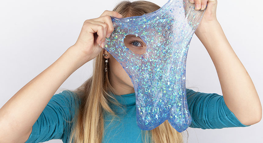 Funny girl holding a glitter slime in front of her face and looking through its hole.