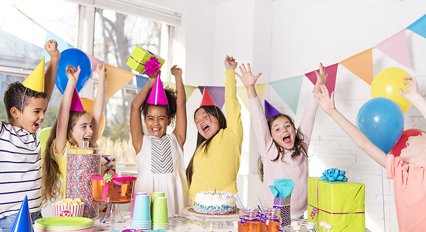 Kids around a table at a birthday party. It has decorations a cake, and candy.  Kids are having fun, their hands in the air.