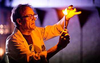 Mad scientist using a lighter to light what's in his hand